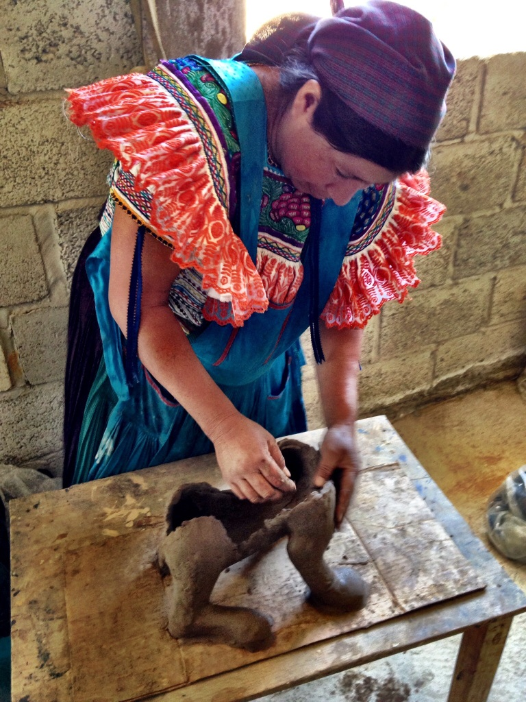 Juana shows how she molds the clay into the shape of a jaguar